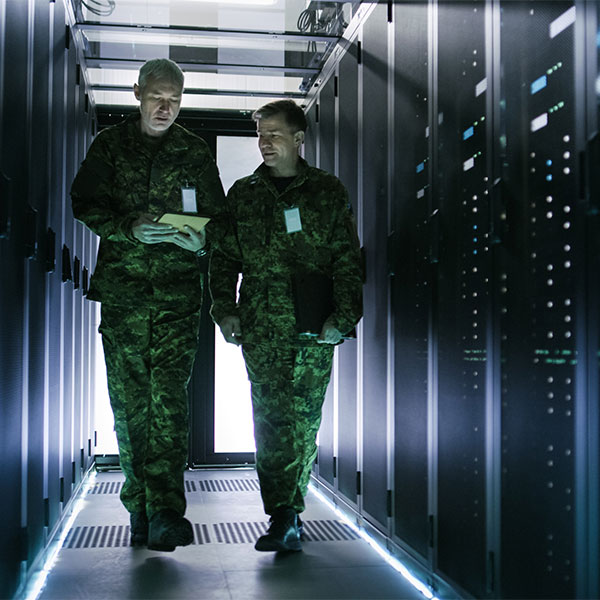 Two miltary men walking through a server room