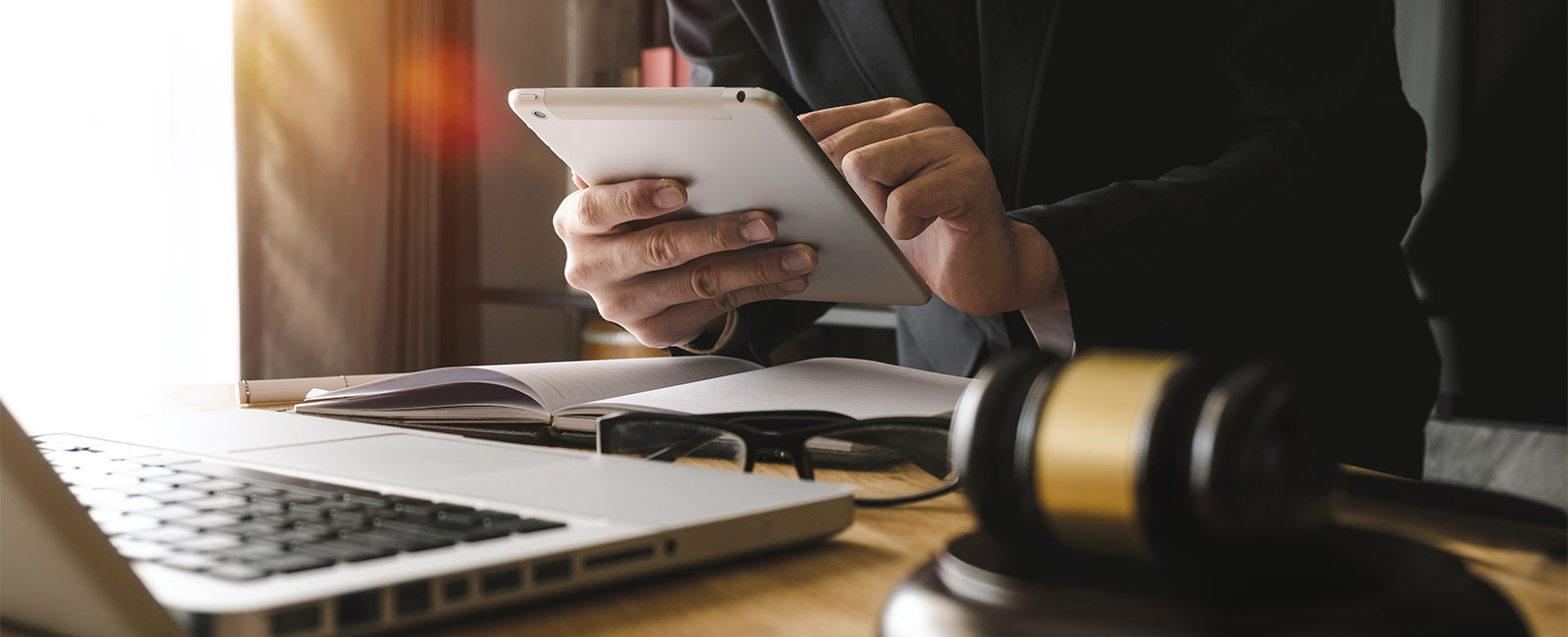 Man using tablet with gavel on table