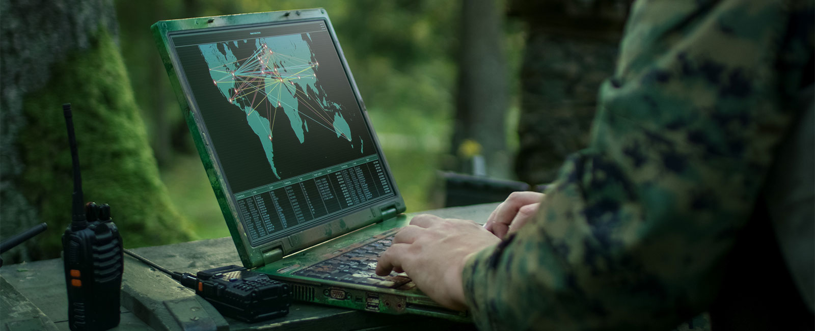 Soldiers using military laptop in forest